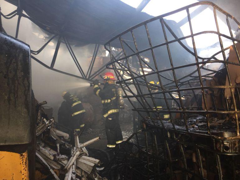 Bomberos intentan sofocar el incendio de bodegas
