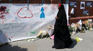 Mujer pasea junto a mensajes pegados en una pared cerca de la escena del ataque de Finsbury Park Mosque, en Londres