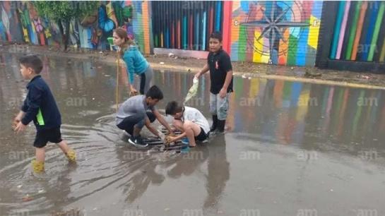 Niños retiran basura de coladeras para evitar una inundación mayor