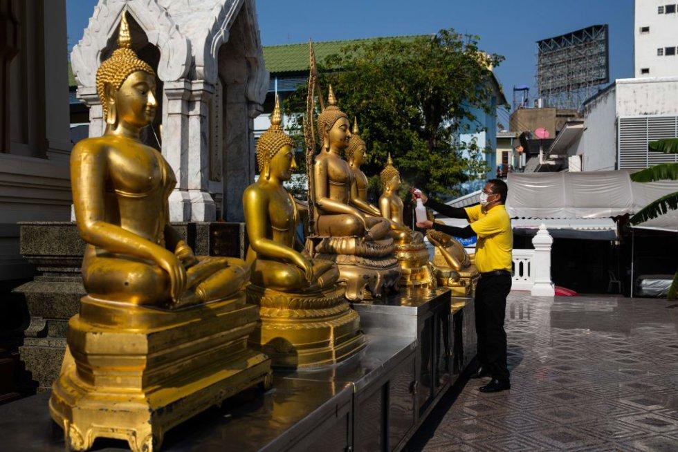 Tailandia. Un voluntario desinfecta las estatuas de Buda antes de presenciar a monjes tailandeses que participan en el canto de una antigua oración diseñada para evitar la plaga en Wat Traimit el 25 de marzo de 2020 en Bangkok, Tailandia