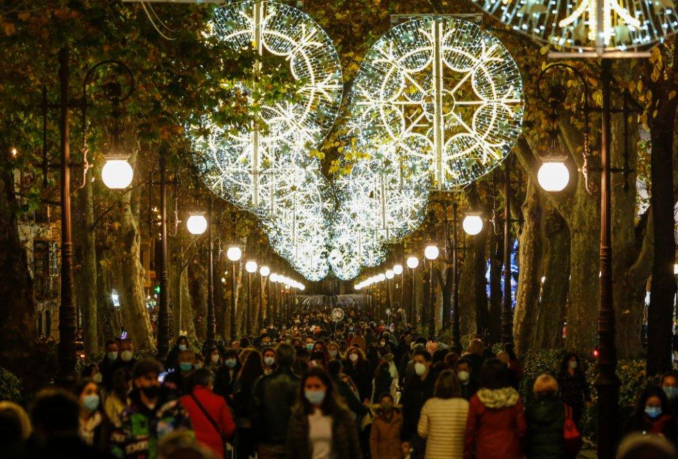 Mucha gente caminando en una calle decorada con luces navideñas en medio de la pandemia en Granada, España