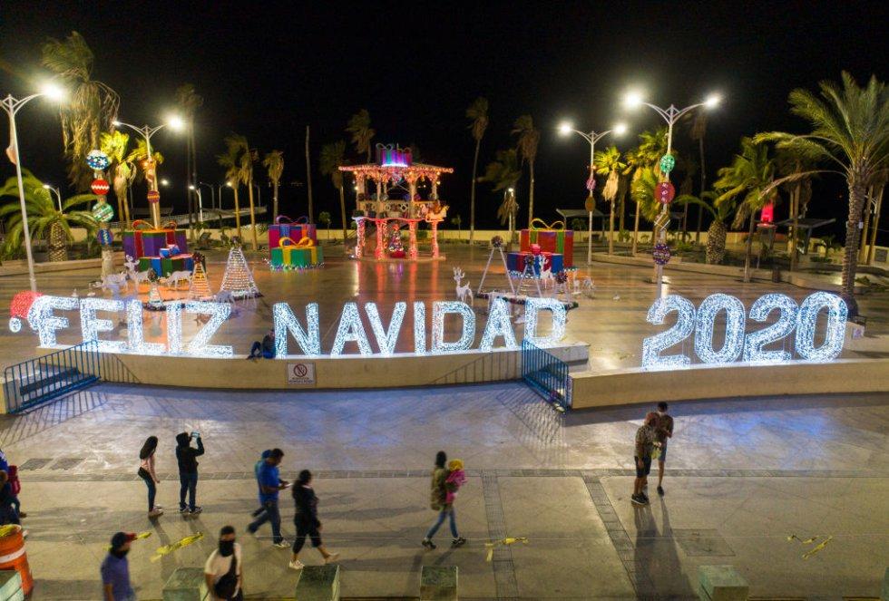 """La gente camina por el paseo marítimo visitando el stand decorado con un gran letrero iluminado de luces y adornos navideños de """"Feliz Navidad 2020"""" como parte de las celebraciones de la temporada navideña el 15 de diciembre de 2020 en La Paz, México."""